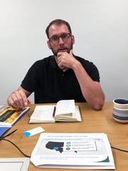 Jon Goldstein, senior policy manager  for U.S. climate and energy for the Environmental Defense Fund, presents background materials on methane emissions during an interview at the Farmington Daily Times office in July.