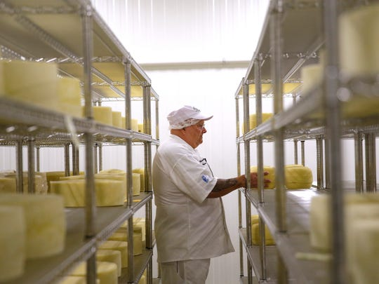Mike Brennenstuhl, master cheesemaker and owner of Door Artisan Cheese Co., pulls a sample of cheese being aged at the Egg Harbor. Door Artisan uses milk from Red Barn Farmily Farms to make its cheeses.