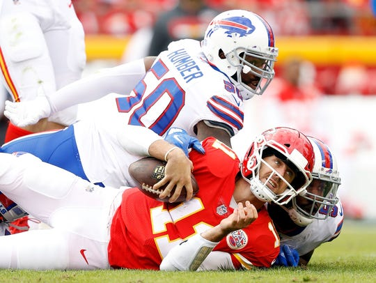 Kansas City quarterback Alex Smith is tackled by Buffalo Bills defenders Jerry Hughes and outside linebacker Ramon Humber (50) during Sunday's game in Kansas City, Missouri.