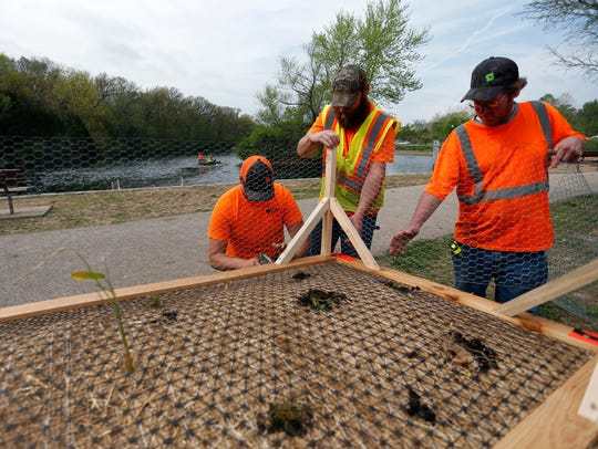 "City of Springfield employees assemble a ""floating artificial wetland"" to put into the lake at Sequiota Park to help control algae in the lake on Wednesday, May 2, 2018."