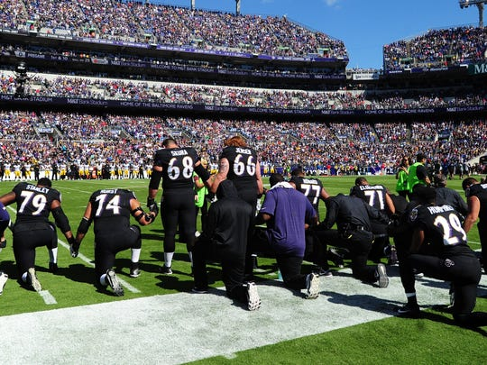 Baltimore Ravens players kneel to pray prior to the national anthem before Sunday's game against Pittsburgh. They stood for the anthem.