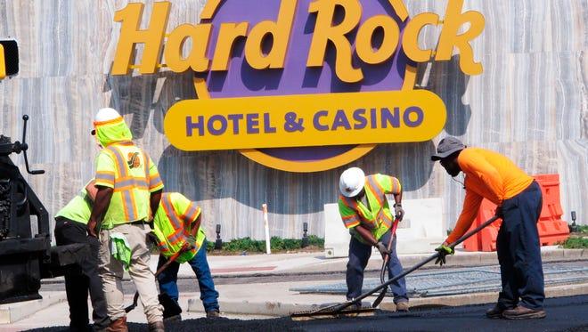 Workers rake asphalt outside the Hard Rock casino in Atlantic City, N.J.