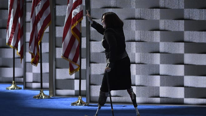 Sen. Tammy Duckworth, D-Ill., waves while arriving on stage during the Democratic National Convention in Philadelphia on July 28, 2016.