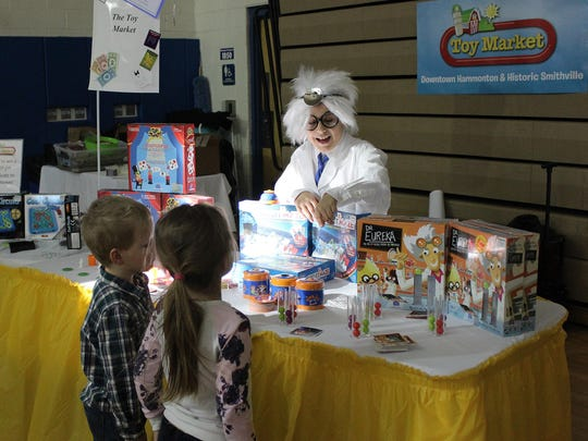 Matthew Donio, dressed as Dr. Eureka, shows Brayden Hulme, 5, (front left) and Brynlee Hulme, 5, (front right) the different games the Toy Market has to offer.