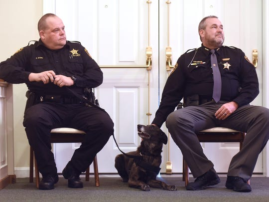Coshocton County Sheriff Tim Rogers pats K-9 officer Henata while Rogers and Detective Dave Stone listen to a speaker during a memorial for Stone's late K-9 partner Dingo.