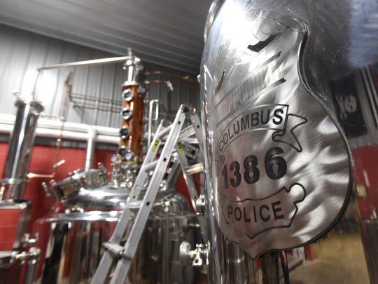 A metal badge honoring the late Columbus Police Department officer Steve Smith on a kettle at Killbuck Creek Distillery in Warsaw.