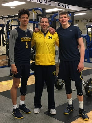 Michigan basketball players D.J. Wilson (left) and Moe Wagner (right) with U-M strength coach Jon Sanderson.