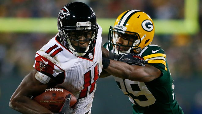 Falcons receiver Julio Jones looks to run after catching a pass against Packers cornerback Casey Hayward.