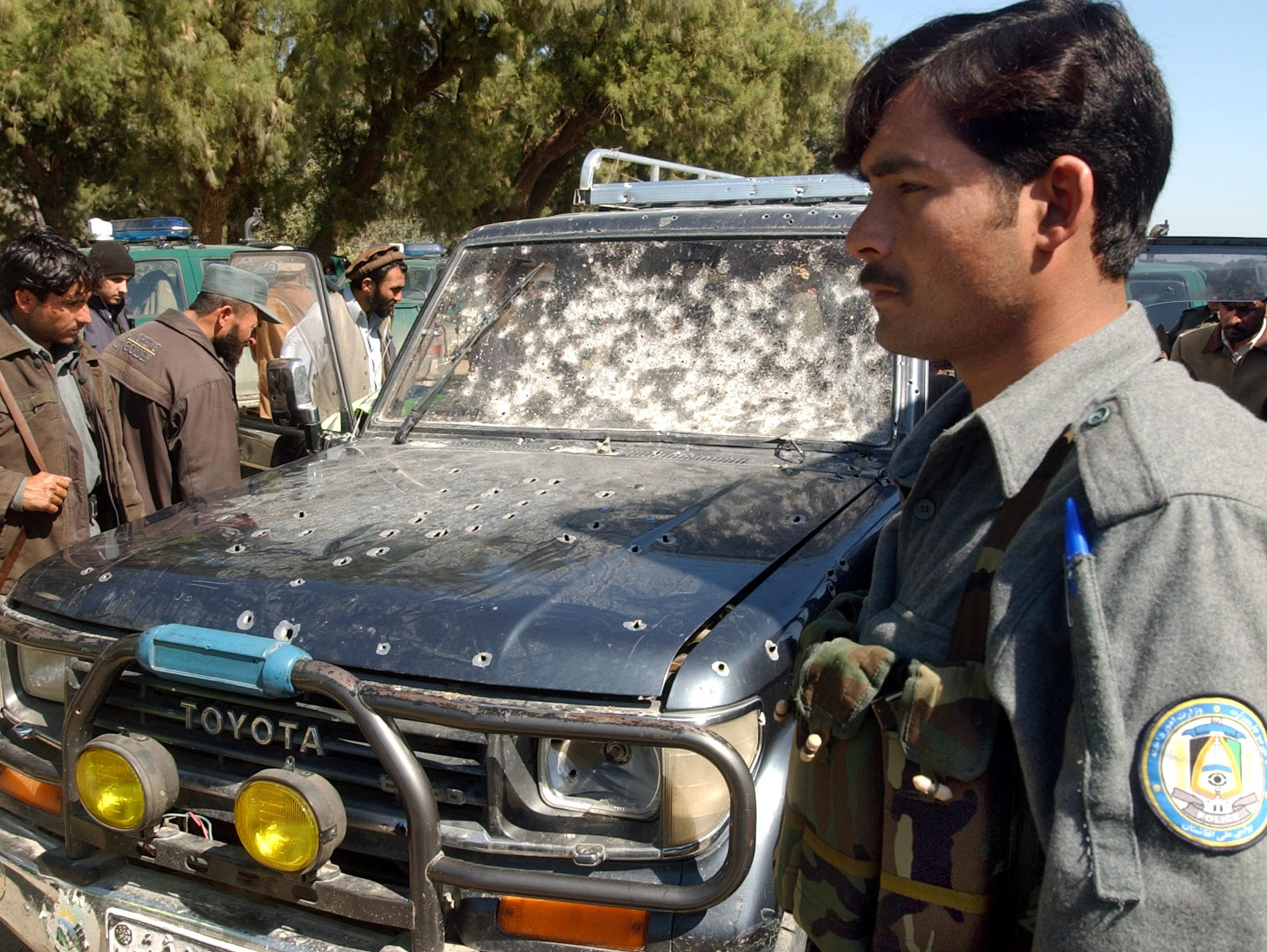 Afghan police inspect the Toyota Prado that targeted