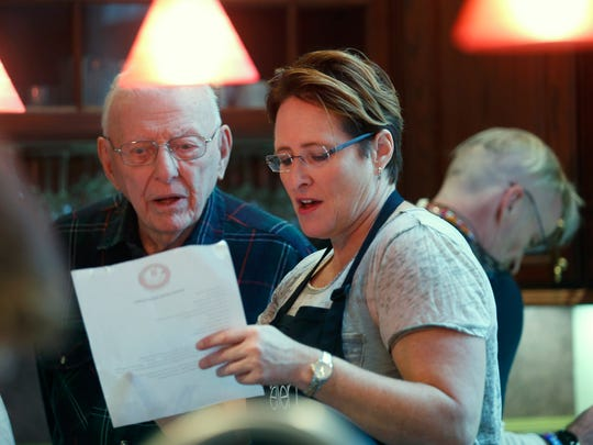 WWII veteran Ralph Edwards, 91, of Pittsford looks at a recipe with Air Force veteran Ellen Adams while joined by others in preparing a meal at the EquiCenter in Honeoye Falls.