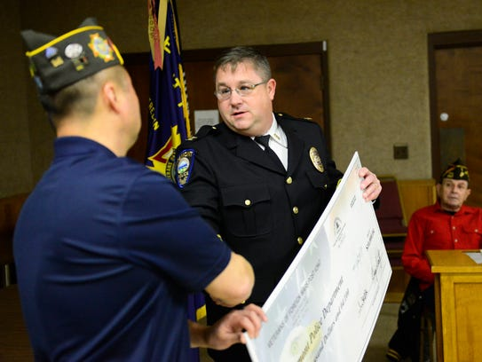 Fremont Police Chief Dean Bliss accepts a check for