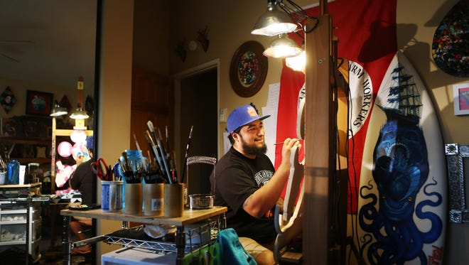 Artist Gustavo Rimada works on a painting in his home studio on Wednesday, April 6, 2016 in La Quinta, Calif.