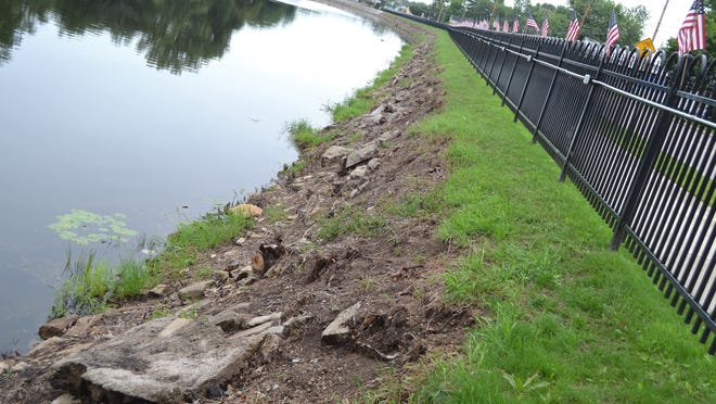 The embankment along the Oconto River behind the new fence was cleared this summer by a group of people recognized by the city of Oconto last week.