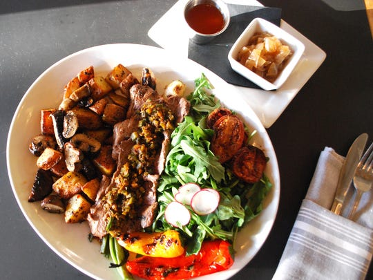 Milk & Honey: Carne Asada steak platter with roasted potatoes, charred peppers and tomatoes, caramelized onions, hot sauce and arugula salad with radishes