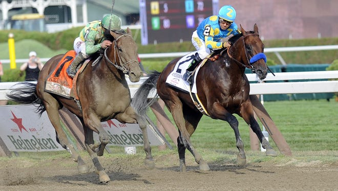 Keen Ice, left, moves past Triple Crown winner American Pharoah to win the Travers Stakes on Aug. 29. Both will compete in Saturday's Breeders Cup.