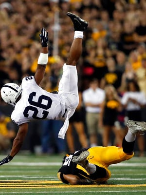 Penn State running back Saquon Barkley (26) is upended by Iowa defensive end A.J. Epenesa during the first half of an NCAA college football game Saturday, Sept. 23, 2017, in Iowa City, Iowa. (AP Photo/Jeff Roberson)