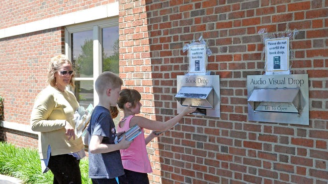 Jamie, Carter, and Julia Flanary return items they've had at home since March to the Wayne County Public Library in Wooster. This week, all of the library's branches started curbside services by appointment for patrons to checkout new materials.