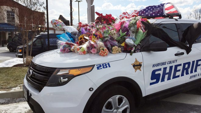 Tributes in memory of two slain deputies are stacked on a Harford County Sheriff's Office Department vehicle outside the department's southern precinct, Thursday morning