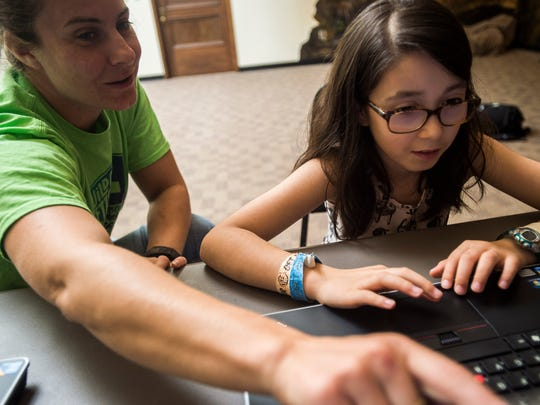 Tech teacher Erica Bertucci helps fourth-grader Scarlet Montesano build a maze game in Scratch, a program designed to introduce kids to coding, part of a free summer program at Fletcher Free Library in Burington.