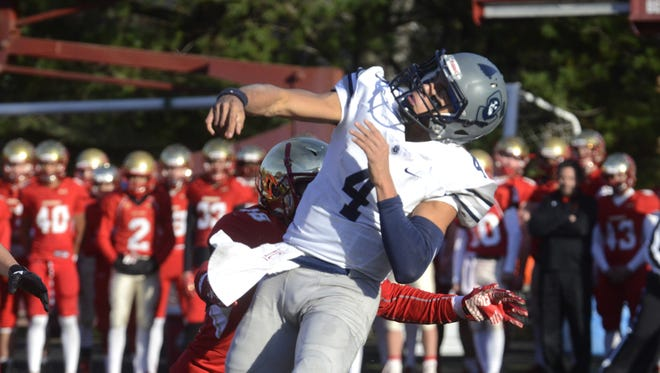 St. Augustine quarterback Josh Zamot unloads a pass just before being hit by Pat Palmer of Bergen Catholic during action in Saturday's Non-Public Group 4 playoff game.
