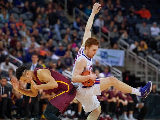 Chicago Loyola's Marques Townes, left, fouls Evansville's Noah Frederking by undercutting him at the Ford Center Sunday afternoon. Loyola beat Evansville 76-66.