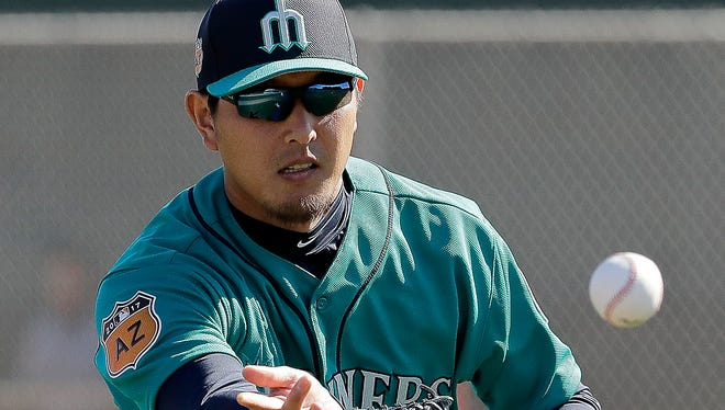 Mariners pitcher Hisashi Iwakuma participates in a fielding drill during spring training. After making 33 starts last season, Iwakuma decided against participating in the World Baseball Classic this spring to get ready for the MLB season.
