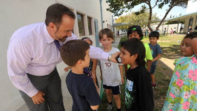 Flory Academy Principal Scott Mastroianni lets kindergartner Emmanuel Juarez listen to his radio as he makes his rounds during lunchtime at the Moorpark school. Mastroianni is in the California Lutheran University superintendent certificate program.