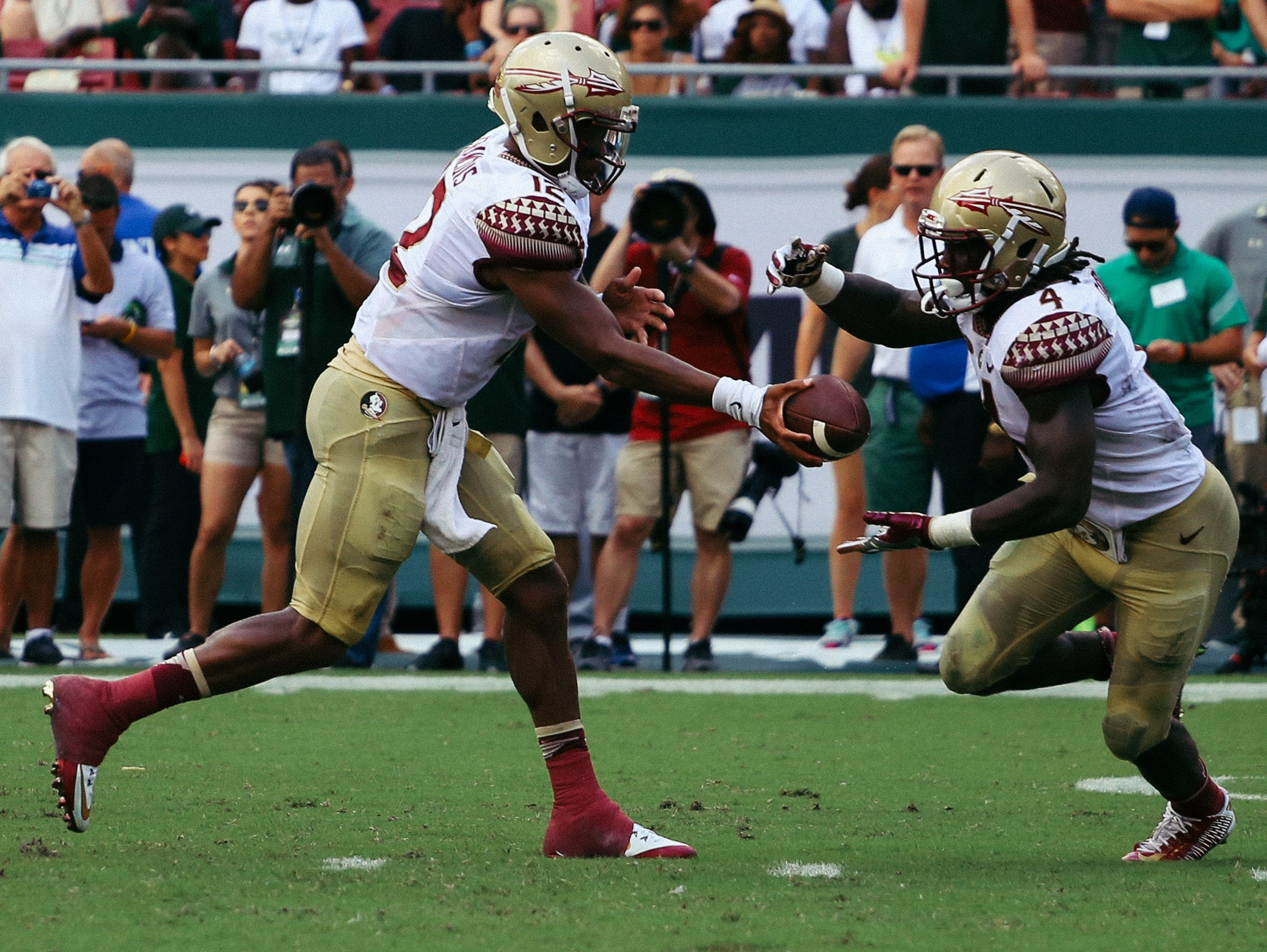 Deondre Francois (12) hands the ball off to Dalvin