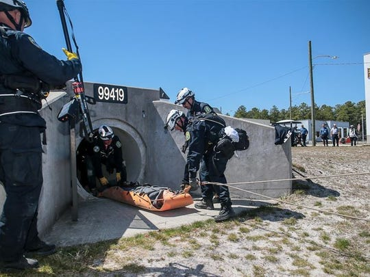 NJ Task Force 1 members recover a victim from a tunnel during Operation Derecho, a full-scale search and rescue exercise hosted by the NJ State Office of Emergency Management at Fort Dix on April 17, 2016.