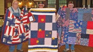 Three veterans from the Yellville American Legion Post receive quilts honoring their service to our country.