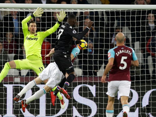 Crystal Palace's Christian Benteke, center, leaps and heads the ball to score the opening goal of game during their English Premier League soccer match between West Ham United and Crystal Palace at the London stadium in London, Tuesday, Jan. 30, 2018. (AP Photo/Alastair Grant)