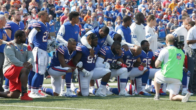 Members of the Buffalo Bills players kneel in protest during the national anthem on Sunday.