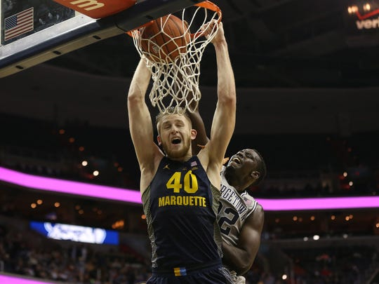Feb 11, 2017; Washington, DC, USA; Marquette Golden Eagles center Luke Fischer (40) is fouled while dunking the ball by Georgetown Hoyas forward Akoy Agau (22) in the first half at Verizon Center.