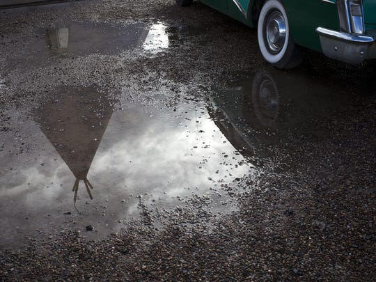 A tepee is reflected in the parking lot of the Wigwam