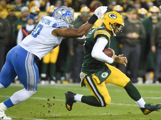 Packers quarterback Brett Hundley runs with the ball as Lions defensive end Cornelius Washington tackles him in the first quarter at Lambeau Field, Monday, Nov. 6, 2017.