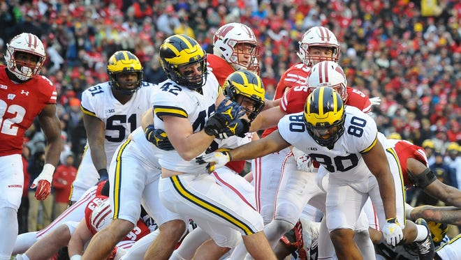 Michigan dropped out of the Amway coaches' poll following Saturday's 24-10 loss at Wisconsin.