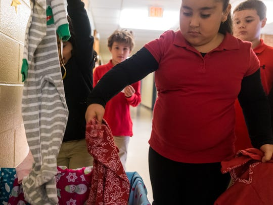 D'Ippolito third graders Amelia Gomez and Gianna Rodriguez  place pajamas in a collection box for a pajama drive for underpriviledged children at D'Ippolito Elementary School on Monday, November 13.