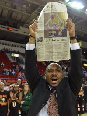 "Donald Nelson holds up a newspaper that displays the slogan of his 2012-'13 team: ""Gold Ball or Bust."" He coached Milwaukee Riverside to the state title that year."