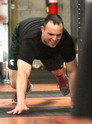 Customer Tom Kill crab-walks across the floor during warmup at CrossFit Menace.