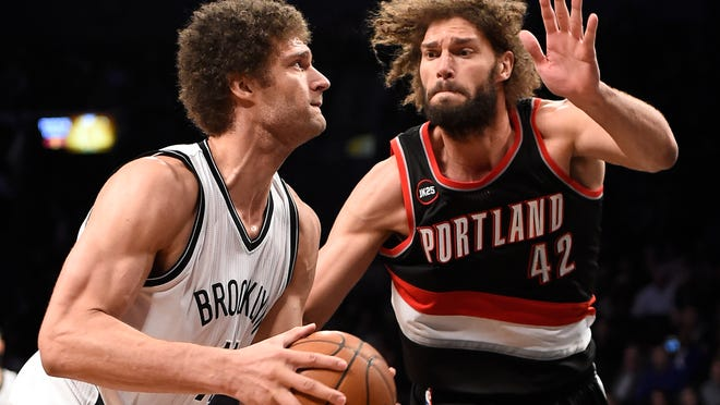 Brooklyn Nets center Brook Lopez (11) takes aim for the basket around his twin brother, Portland Trail Blazers center Robin Lopez (42), in the second half of a game Monday, April 6, in New York. The Nets won 106-96.