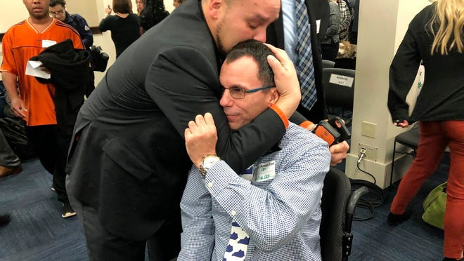 Eric Crawford, center right, is hugged by another medical marijuana advocate after a bill to legalize medical cannabis in Kentucky was approved by a state House committee Wednesday in Frankfort, Ky. Kentucky House Speaker David Osborne says the bill could possibly come up for a House vote as soon as this week.