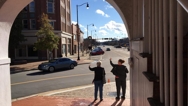 Two anti-war protesters hold up peace signs to drivers at the Market House on Saturday, Jan. 4, 2020.