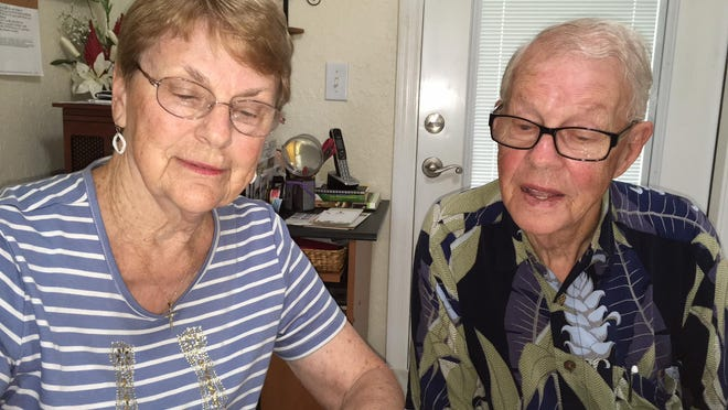 Shirley and Elbern Freeman look over a scrapbook on a recent day in their Ocala home.
