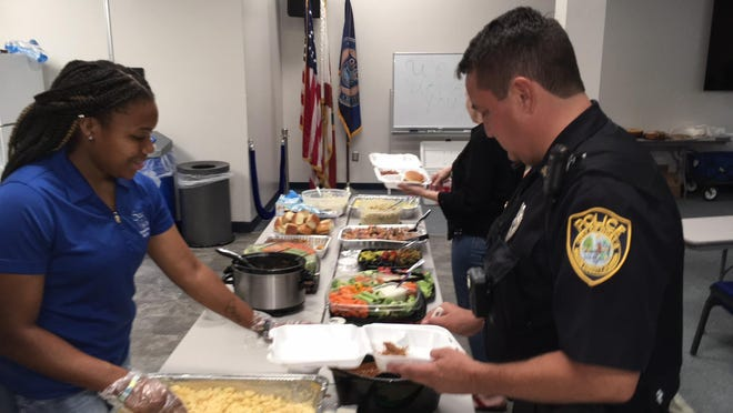 Tiara Hutchinson, youth mentor with Sozo Kids outreach of Help Agency of the Forest, serves lunch on Wednesday at the Ocala Police Department.