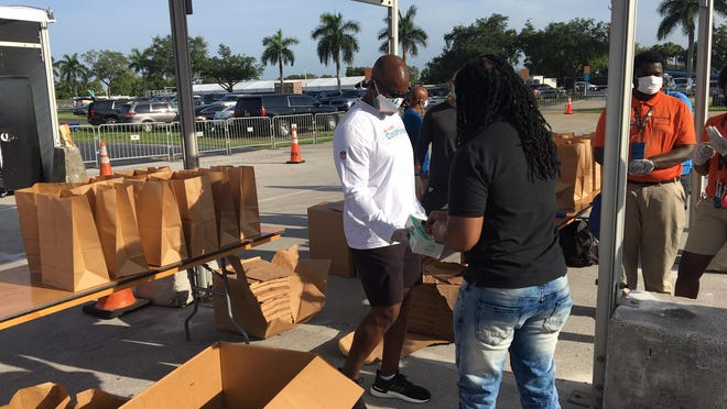 Miami Dolphins coach Brian Flores helped provide meals to families on Monday at Hard Rock Stadium.