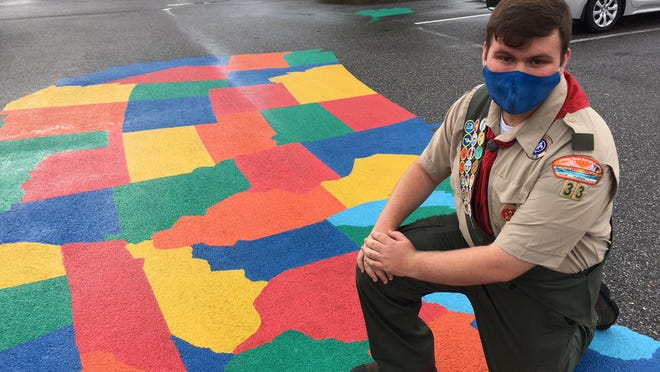 Joshua Coogle kneels near the United States map he created outside Brentwood at Fore Ranch.