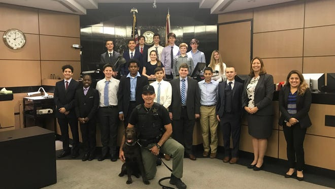 Students enrolled in The King's Academy's O'Keeffe Pre-Law Studies Program Mock Trial class enjoyed meeting K-9 Officer Guko, a chocolate lab, during the Florida Middle School Mock Trial competition.