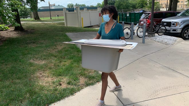Freshman Evelyn Trumpey carries her belongings into her dorm room at the College of Wooster on Tuesday. Students and their families were required to wear masks.