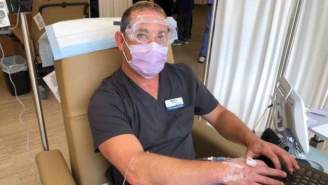 """Mike Lewis, director of nursing at Heartland of Dublin, receives an infusion as part of the antibody trial. """"It really didn't feel any different than an IV,"""" he said."""