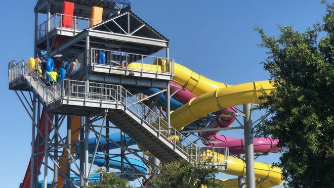 Visitors climb up to the top of a water slide at Typhoon Texas, which reopened May 29 after being closed because of the coronavirus pandemic.